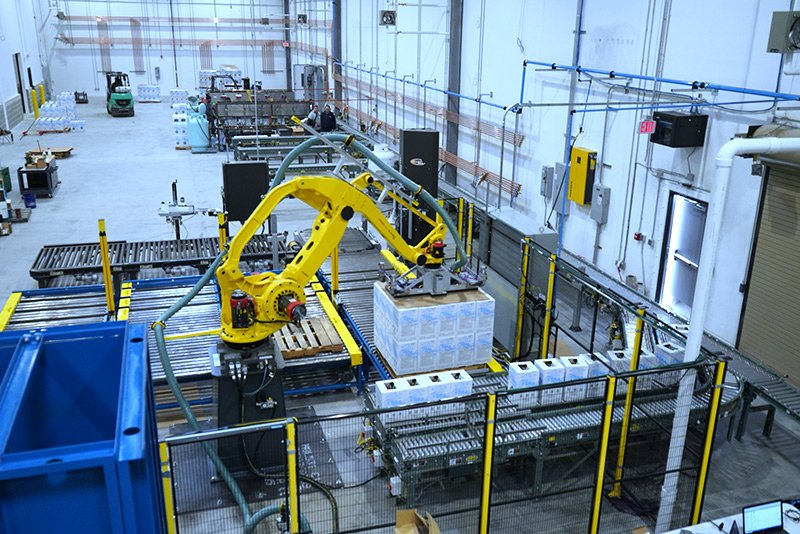 Robotic Carton Palletizing System including Fanuc M410iB/140H palletizing robot with indeed from Hytrol EZ Logic 24 volt zero pressure accumulation conveyor and Hytrol 138 ACC powered accumulating roller conveyor. Alba pallet dispenser, Alba CDLR pallet conveyor and Alba 3 strand chain transfer conveyor used to send palletized load to Wulftec WCA Smart stretch wrapper.