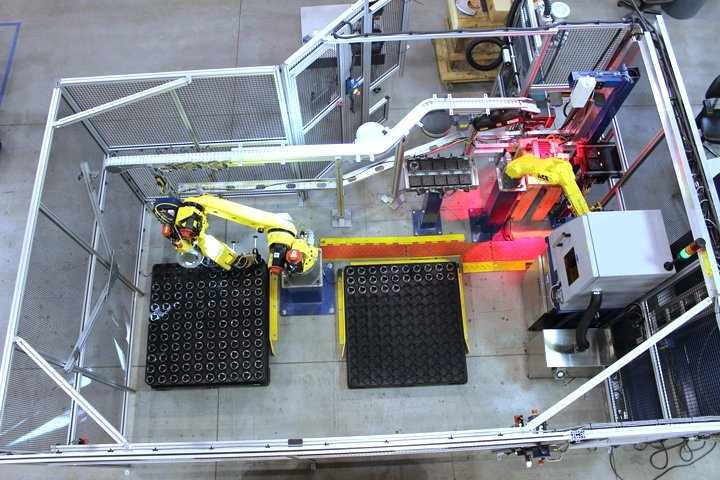 FANUC M-20iA robot de-palletizing semi-organized trays of automotive parts and placing the parts onto a conveyor for processing in a grinder. After grinding, the parts are brought back into the cell, laser marked and then placed back into trays for removal by a fork truck. An on-board camera on the M-20iA robot uses FANUC iRVison to scan and locate parts within the trays. The M-20iA robot also handles the empty trays during de-palletizing operation as well as palletizing the finished parts. A FANUC LRMate 200iD/7L robot is used to tend the laser marking system.