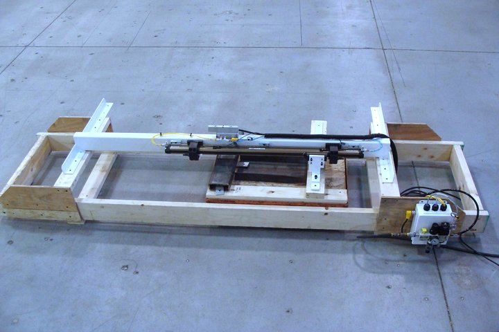 """Door Opener for CNC Machines setup on a test fixture. The air operated cylinder and mounting structure is fixed to the main wooden frame (simulating mounting the unit to the top of the CNC machine) and the """"tow bar"""" is attached to a weighted cart simulating the mass of the door on a CNC machine."""