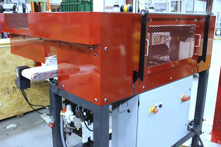 Left front view of the Model FL3600 Furnace Loader. Note: The black handle shown is for raising the transfer plate assembly during docking and removal of the FL3600 Furnace Loader at a sinter furnace. The interlocked access panel with pull handles shown is removed when accessing the pusher rake for changeover.