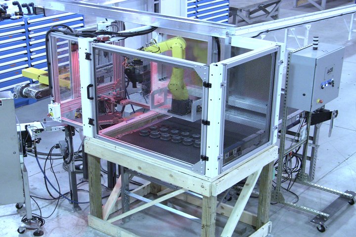 Right front view of the Model 100A Furnace Loader. Note: The Model 100A's compact frame mounts directly on top of the sinter furnace load table (shown on a wooden mock-up here) freeing up valuable floor space.