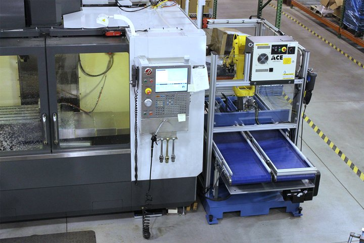 Model RMT positioned on the right hand side of a CNC vertical machining center. Note: The narrow and compact size of the RMT, providing efficient use of floor space. A second machine tool may also be placed to the right of the RMT for even greater production efficiency.