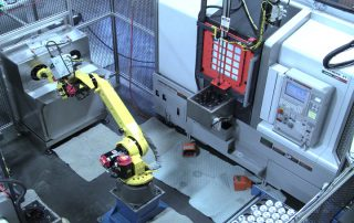 FANUC M-20iA robot tending a lathe and transporting machined components to a wash/dry system for cleaning. The wash/dry system consists of a stainless steel enclosure with separate wash and dry chambers. High pressure nozzles direct multiple streams of de-ionized water at the part being cleaned. A high pressure blower dries the part. The robot provides part manipulation for both the washing and drying cycles. Parts are immediately assembled and packaged after the cleaning process.