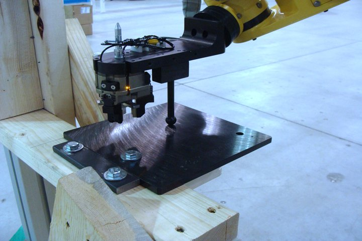 RoboCart performing a calibration routine after being removed and re-installed on a machine tool. The FANUC LRMate 200iD/7L robot is using FANUC iRCalibration software to touch on 3 different planes located on the machine tool to accurately master the user frame and tool center point for the cell without having to manually touch up points.