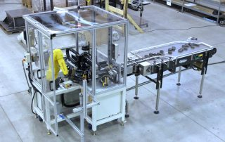 FANUC LRMate 200iD robot with dual end of arm tooling assembling automotive components for a weld station. Parts are bulk loaded to a Bi-Flo accumulation table, where they are accumulated and feed into the robot cell. A second part is dispensed to the robot with a coin feeder mechanism. The robot assembles both components and presents the assembly to the weld station for welding. This cell is constructed using our RoboCart modular automation platform.