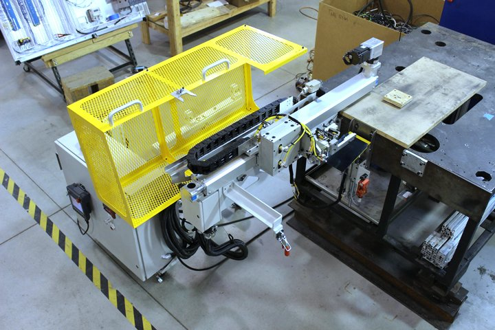 Model SE Press Takeout mounted to a test bench. Note the roll over guarding provides easy access to the press takeout. The storage/removal cart is shown in the back ground.