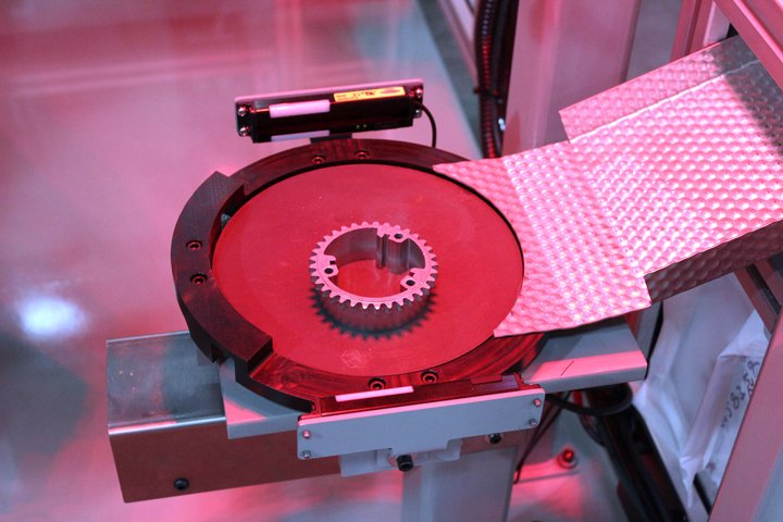 An available aux axis servo-driven rotary turntable on the Model 220 Sizing Press Loader, which is used to orient the part prior to sizing press load. The servo turntable allowed for more degrees of part rotation than the robot end of arm tooling could provide. The part had only one orientation for correct loading into the sizing press.
