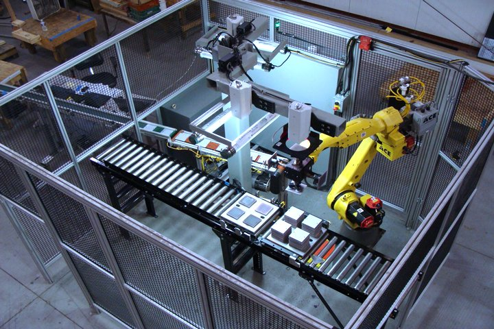 FANUC M-20iA robot with a dual iRVision camera setup palletizing fragile parts onto a tray. A multi-headed vacuum end of arm tool picks multiple parts and then places them onto a tray in a pre-determined pattern. Spacers are placed in between parts in a known sequence, creating the desired tray load. A custom infeed conveyor with individual lift stations provides no part to part contact for parts entering the cell.