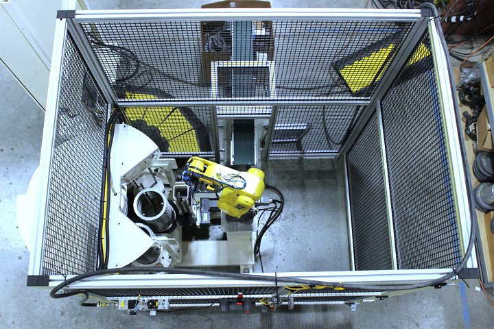Top view of the Model WS8100 Mate Machine Tender with safety enclosure. Note: The WS8100 Mate uses very little floor space and can be placed next most machine tools. Parts exit this cell on a belt conveyor, which feeds a process machine.