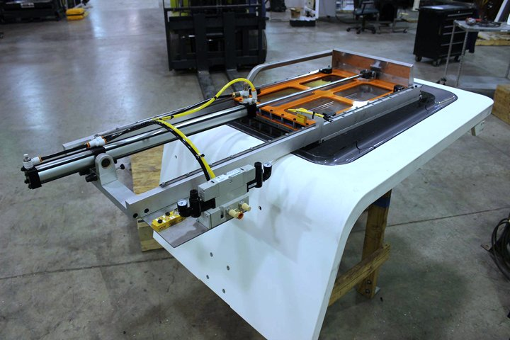 Front door mounted Auto Door (Note machine front door lying on its side for Auto Door installation). The Auto Door features: pneumatic door cylinder, heavy duty shock absorbers for open/close motions, precision guidance, open/close sensors, door closed safety switch and connection cables. Modification of the machine door is required when mounting to the front machine door and includes reuse of the door glass (re- installed in the Auto Door).