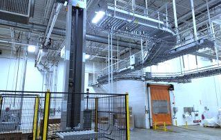 Qimarox PRORUNNER Mk 1 Vertical Conveyor feeding raised Hytrol EZ Logic 24-volt zero pressure accumulation conveyor line