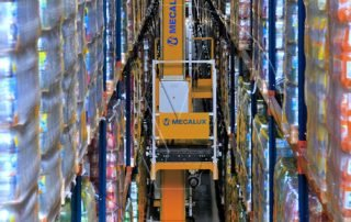 Mecalux stacker crane working in between storage racking for an ASRS system in a bottling distribution center