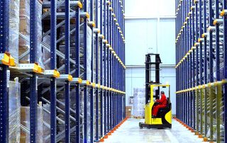 2 rows of Interlake Mecalux Drive in Pallet Racking with fork truck operator retrieving product in a storage facility
