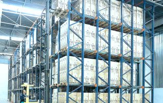 Interlake Mecalux Drive in Pallet Rack Unit in warehouse facility with fork truck operator inserting product into top row
