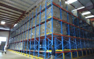 Angle view of a pallet flow rack system filled with palletized cartons being stored in a warehouse with 2 operators working