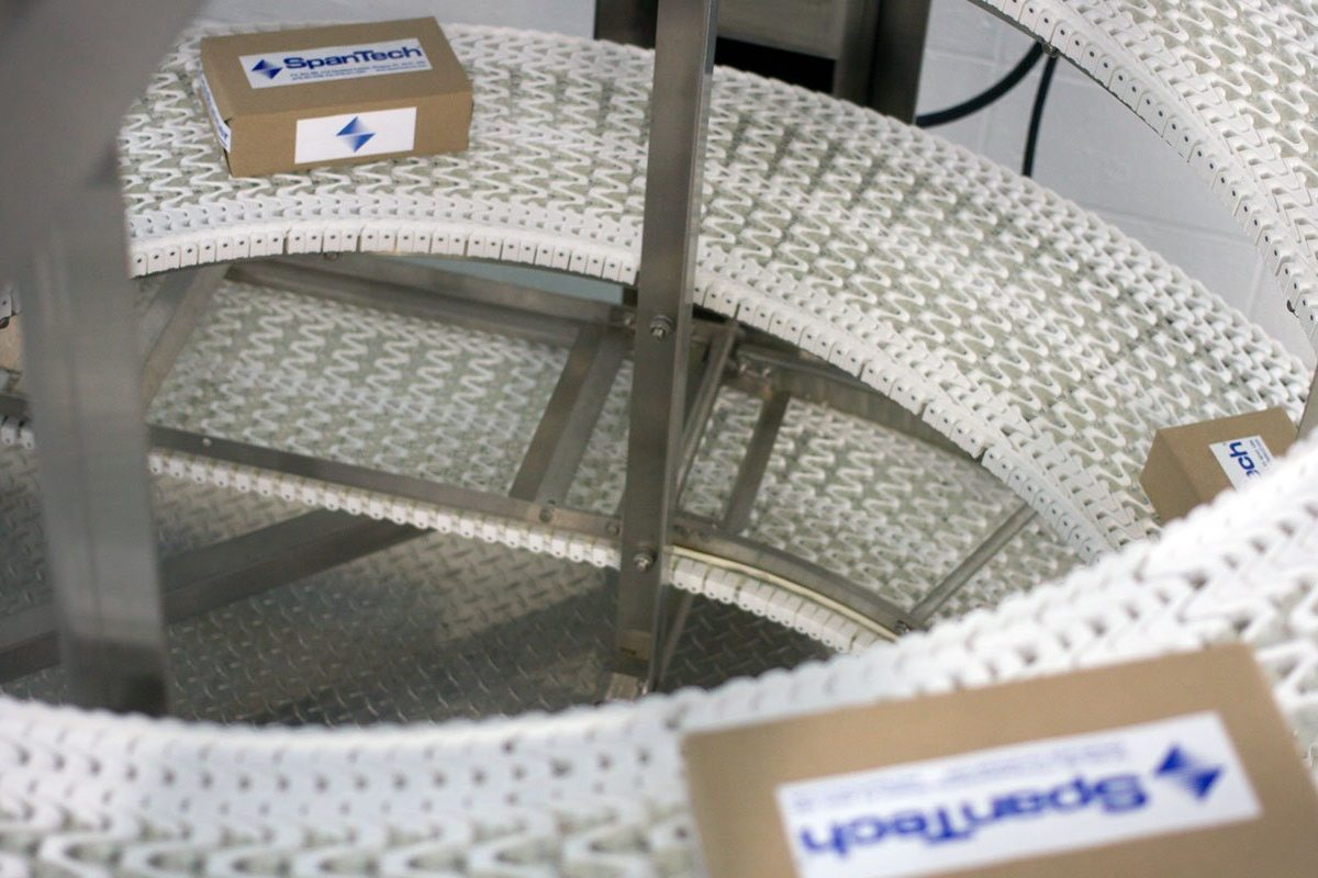 Overhead view of Spantech Vertical Spiral Conveyor moving boxed product down the line