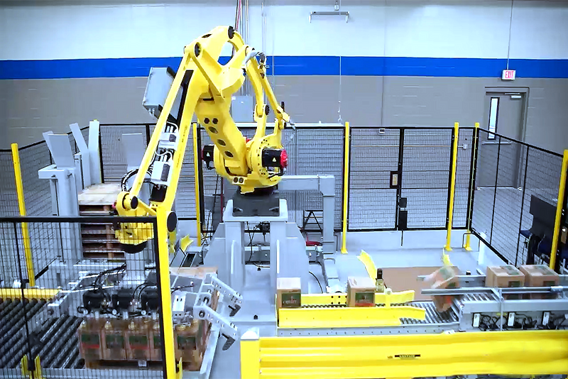 Robotic palletizer placing cases onto pallet load.